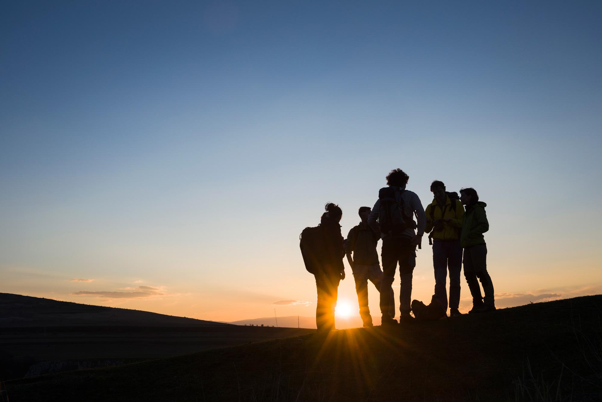 EKT Dialog: Gruppe von Menschen im Sonnenuntergang